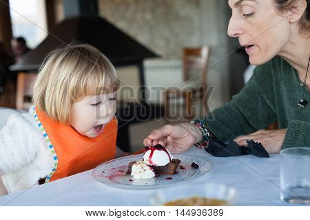 Surprised Face Child Eating Cake With Mother