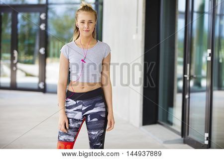 Portrait of confident fit woman listening to music through earphones on footpath