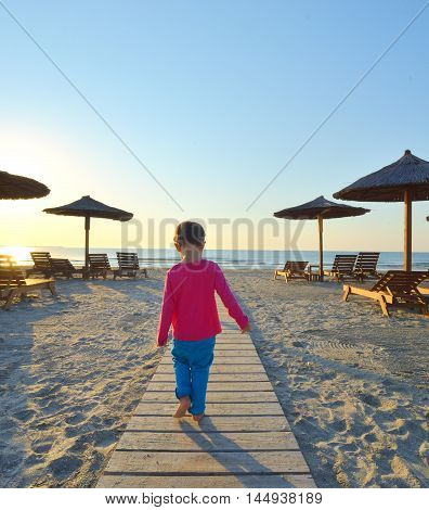 little girl goes on board road among sand