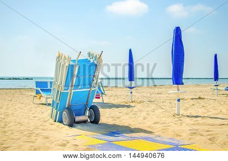 end of summer beach deckchair closed umbrella