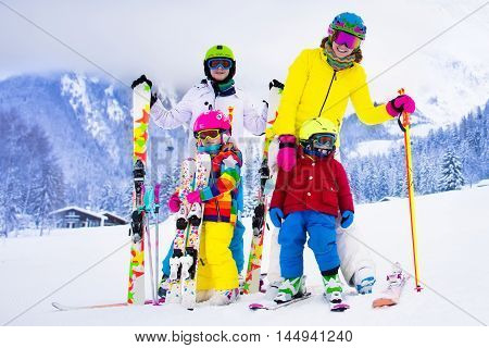 Mother and children skiing in the mountains. Active mom and three kids with safety helmet goggles and poles. Ski lesson for young children. Winter sport and snow fun for family. Child learning to ski