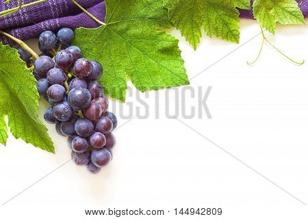 Grapes with grapevine arranged as a top frame around white background. Top view with plenty of copy space
