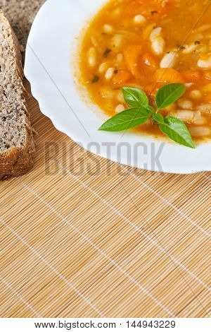 Cooked beans served in white plate with basil leaves and whole wheat bread on wooden background. Plenty of copy space