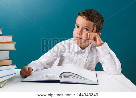 Cute boy with book at the table blue background