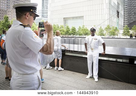 NEW YORK MAY 27 2016: A US Navy sailor has his picture taken at the reflecting pools at One World Trade on the National September 11 Memorial site during Fleet Week 2016.