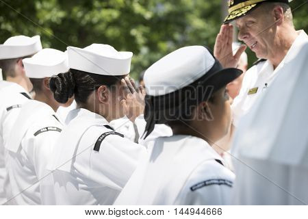 NEW YORK MAY 27 2016: US Navy personnel salute Admiral Phil Davidson, Commander, US Fleet Forces Command, during the re-enlistment and promotion ceremony at the National September 11 Memorial site.
