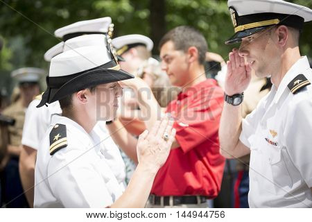 NEW YORK MAY 27 2016: US Navy sailor receives her promotion insignia during the re-enlistment and promotion ceremony held at the National September 11 Memorial site during Fleet Week 2016.