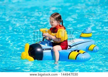 Little girl playing with inflatable toy airplane with water gun in outdoor swimming pool on hot summer day. Kids learn to swim. Children wearing sun protection rash guard relaxing in tropical resort
