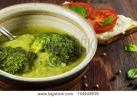 fresh green broccoli vegetable soup and tomato bread as a side dish on a rustic wooden table meal with low calories to lose weight selected focus narrow depth of field