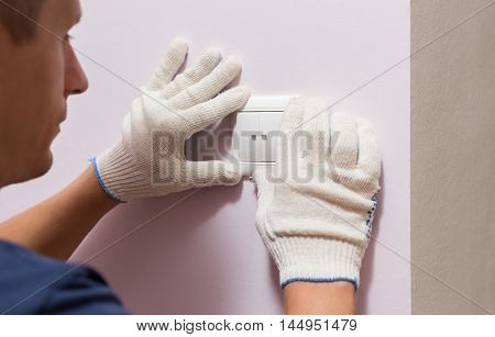 Electrician installing light switch, close up photo.