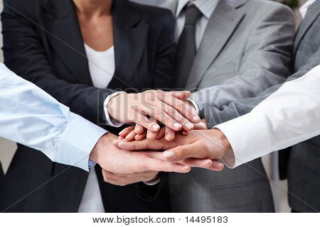 Image of business people hands on top of each other symbolizing support and power