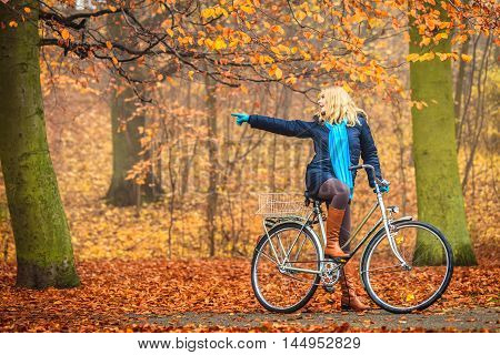 Active Woman Riding Bike In Autumn Park.