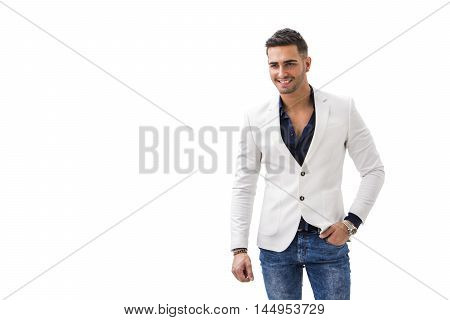 Handsome young man in blue shirt, white jacket and jeans posing isolated on white background in studio
