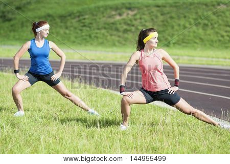 Healthy Lifestyle Ideas and Concepts. Two Young Caucasian Girlfriends in Athletic Sportswear Having Trunk Bending Exercises.Horizontal Shot