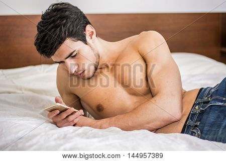 Handsome young man in bed typing on cell phone, sending text message or dialing number