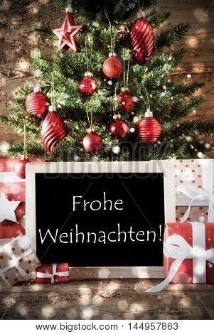 Christmas Tree With Balls And Snowflakes. Gifts Or Presents In The Front Of Wooden Background With Bokeh Effect. Chalkboard With German Text Frohe Weihnachten Means Merry Christmas