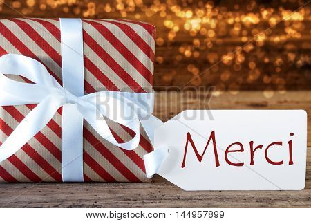 Macro Of Christmas Gift Or Present On Atmospheric Wooden Background. Card For Seasons Greetings, Best Wishes Or Congratulations. White Ribbon With Bow. French Text Merci Means Thank You