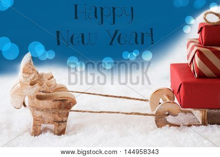 Moose Is Drawing A Sled With Red Gifts Or Presents In Snow. Christmas Card For Seasons Greetings. Blue Background With Bokeh Effect. English Text Happy New Year