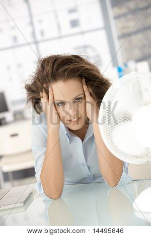 Young attractive woman sitting in office front of fan, feeling hot, cooling herself.?