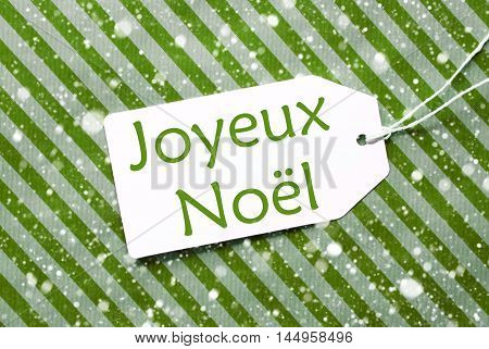 One Label On A Green Striped Wrapping Paper. Textured Background With Snowflakes. Tag With Ribbon. French Text Joyeux Noel Means Merry Christmas