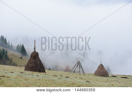 Haystack on a mountain meadow. Autumn fog in the mountains. Rural landscape a cloudy day. Carpathians, Ukraine, Europe