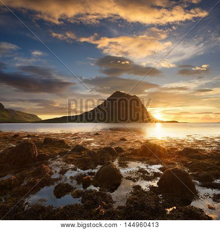 Landscape with a beautiful sunrise and the mountain. Algae on the ocean floor at low tide. Tourist Attraction Iceland. Kirkjufell mountain near the Grundarfjordur town. Beauty in nature