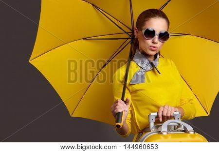 Glamour woman under yellow umbrella and suitcase