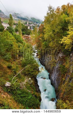 Old Georgia attractions. Stone medieval towers and houses. Mountain river in the gorge. Mestia City. Caucasus, Georgia, Zemo Svaneti
