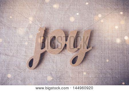 Joy word on fairy light toning background