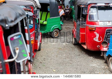 HIKKADUWA - NOVEMBER 14, 2015 SRI LANKA : Tuk-Tuk driver read newspaper between different colored vehicles