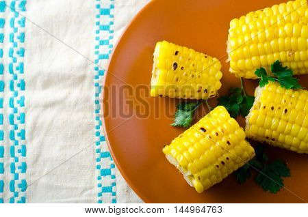 Grilled sweet corn cobs on brown plate with dill, ethnic background