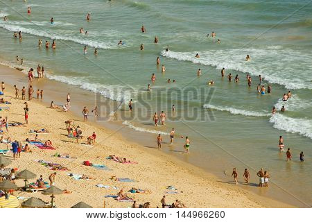 ALBUFEIRA, PORTUGAL - AUGUST 25, 2016: People at the famous beach of Falesia in Albufeira. This beach is a part of famous tourist region of Algarve.