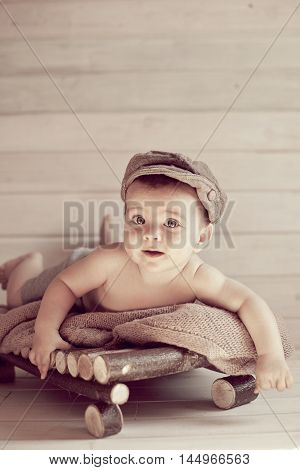 Adorable happy baby boy in a bright room. The baby in the hat smiling looking at camera. Retro style