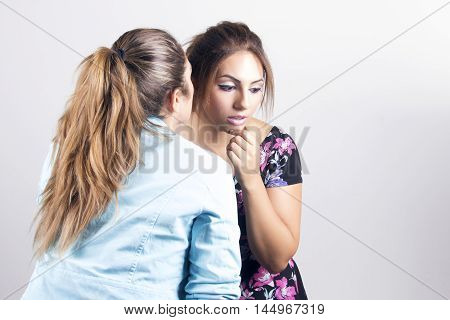 Two latin women gossiping whispering something a secret or bad news. Over a grey background.