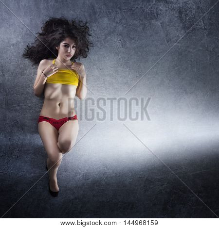 Female model with yellow top and red short and nice body, black long hair laying on the ground with nice background gray texture.