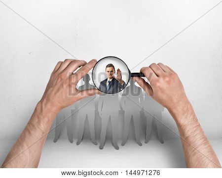 Close-up view of a man's hands focusing magnifier on a businessman with his hand raised. Body language. Stop sign. Employment issues.