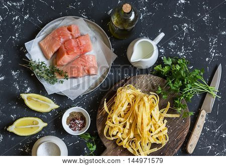 Ingredients for cooking lunch - raw salmon dry pasta tagliatelle cream olive oil spices and herbs. On a dark background top view