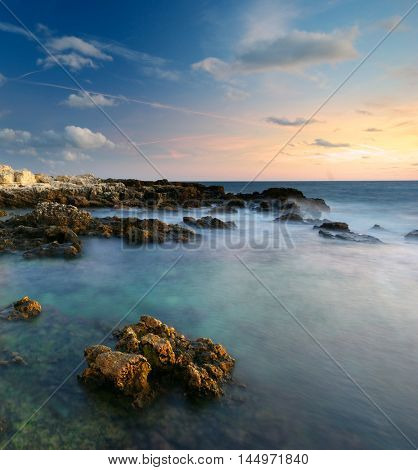 Beautiful seascape. Sea and rock at the sunset. Nature composition.