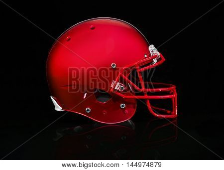 Side view of a red football helmet on a black background