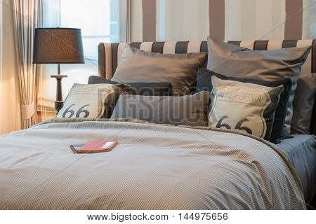 Cozy Bedroom Interior With Dark Brown Pillows And Reading Lamp On Bedside Table