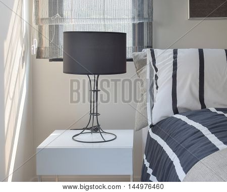 Ready lamp with black shade lamp on bedside table with striped pattern bedding