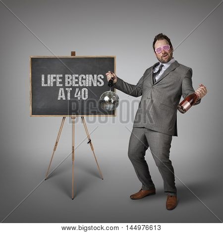 Life begins at 40 text on  blackboard with drunk businessman
