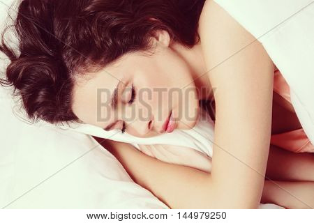 Vintage style close-up shot of young beautiful woman sleeping in bed