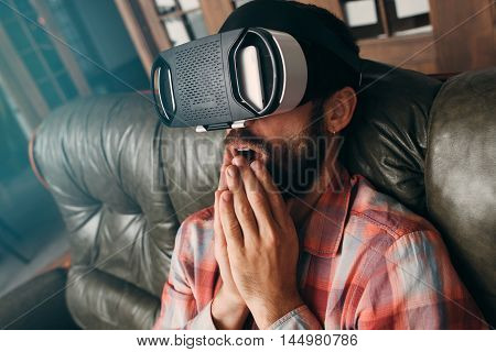 Shocked man with virtual reality glasses. Male watching exciting video in vr headset, impressive 3d technology. Cinema at home, innovation, cyberspace, entertainment concept