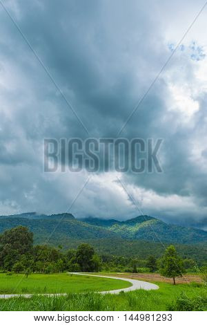 Curved road big trees distant mountains and dark cloudy sky at Huay Tung Tao Chiang Mai Thailand