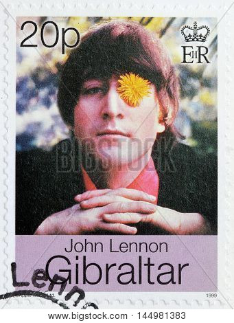 LUGA RUSSIA - AUGUST 19 2016: A stamp printed by GIBRALTAR shows image portrait of famous English musician composer singer and songwriter John Lennon circa 1999.