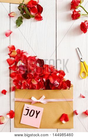 Handmade joy message with flowers, copy space. Paper, scissors, envelope and red rose petals composition with joyful note, white background, free space
