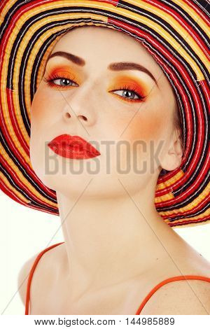 Vintage style shot of young beautiful woman with fancy orange make-up and striped  hat