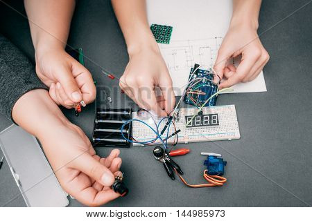 Hands of engineers connecting electronic components. Workplace of electrician working with modern technologies, creation of engineering construction