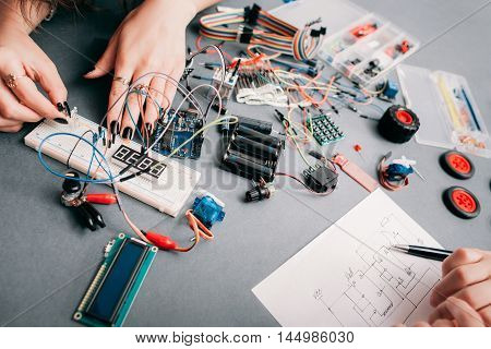 Electronics engineering according to scheme. Electricians creating electronic construction on workplace with special components with wiring diagram